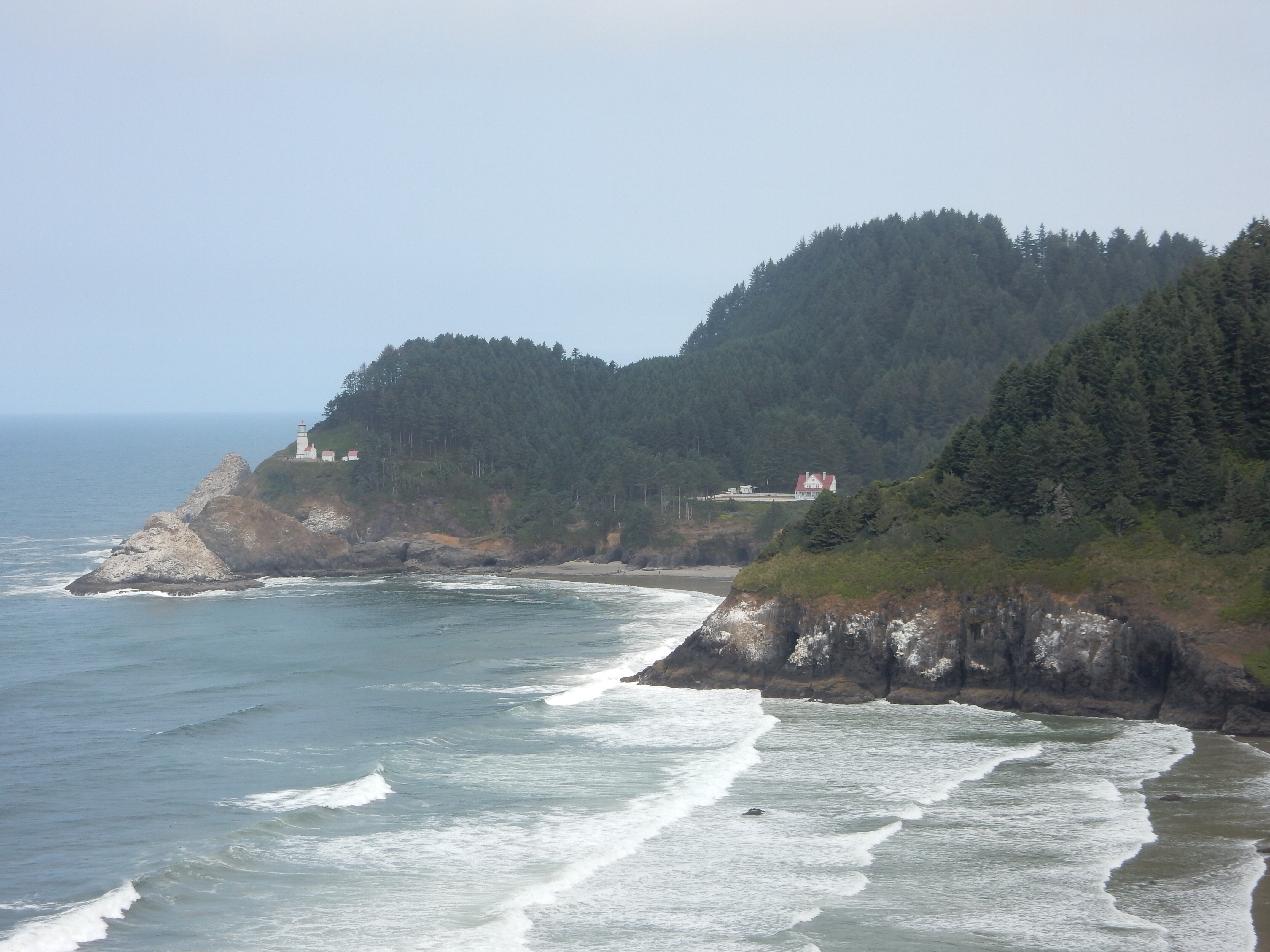 A distant look at the Heceta Head lighthouse and caretaker residence.