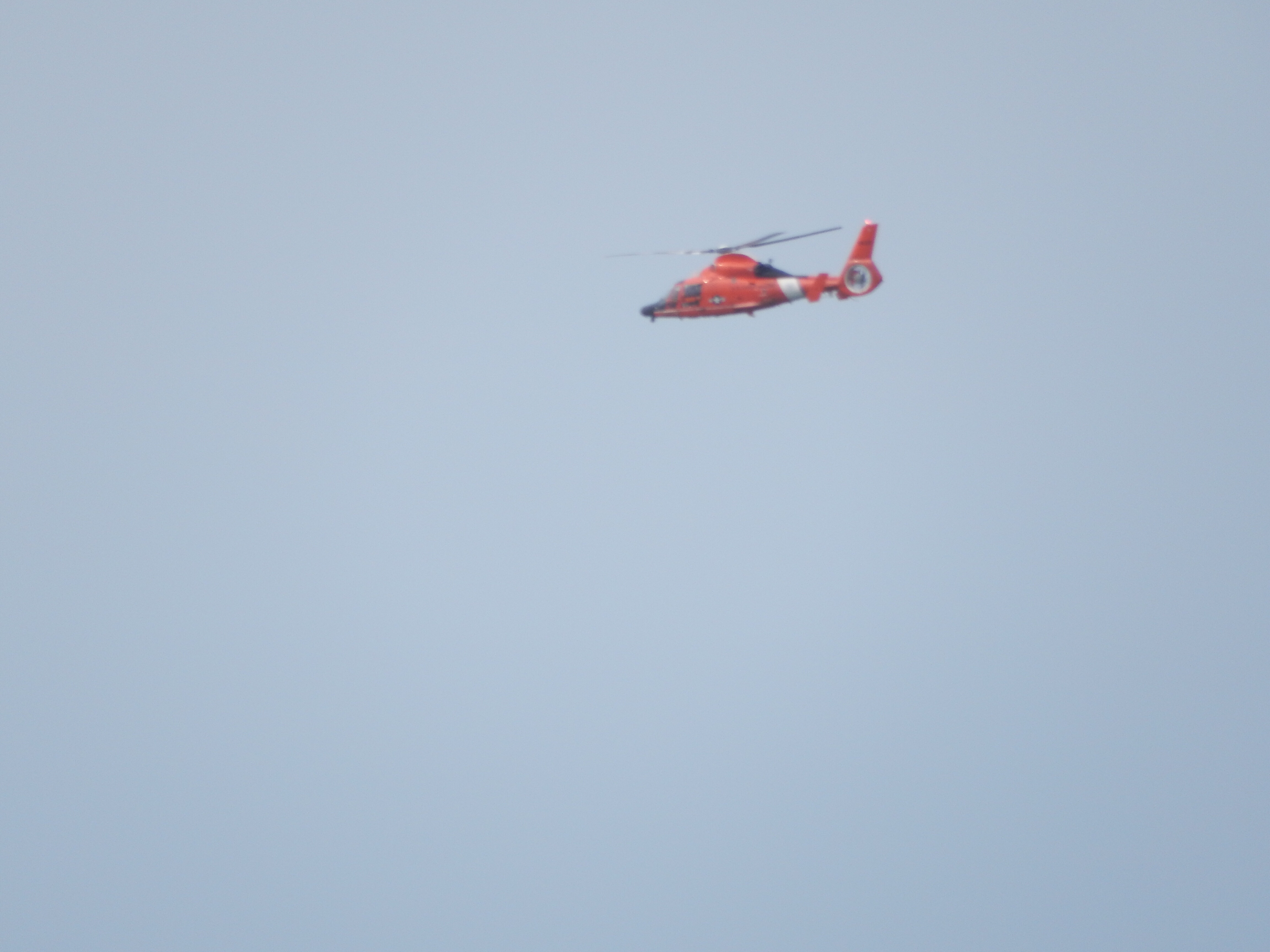 A poor shot of a US Coast Guard chopper heading south along the coast in a hurry.