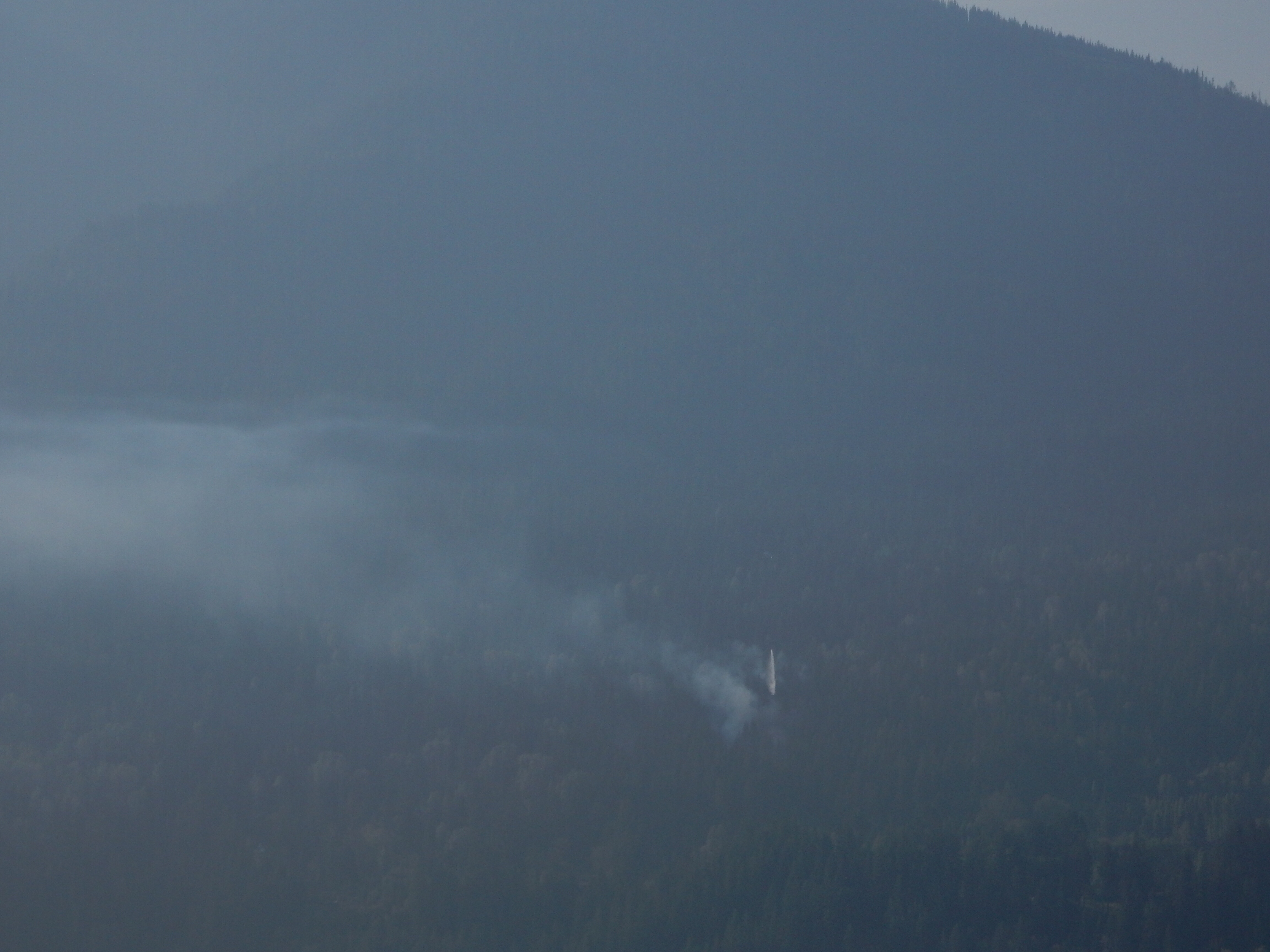 A helicopter drops a load of water on the power line fire north of Balfour, as seen from the Kootenay Lake ferry.