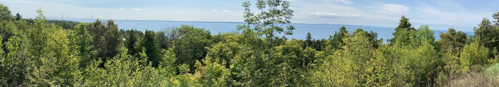 A panoramic view of the Straits of Mackinac, which the Mackinac Bridge to the extreme left.